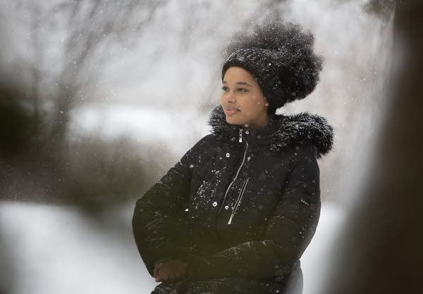 A person sits outside in the snow.