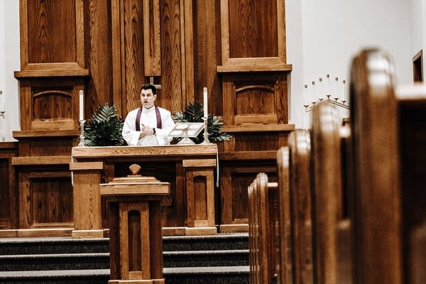 A man preaches at the front of an empty church.