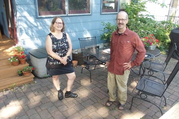 Two people stand on a patio in a backyard.