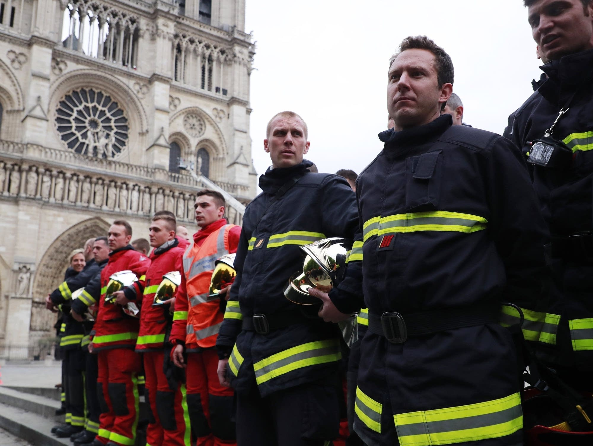 French firefighters wait outside Notre Dame in Paris on Tuesday.