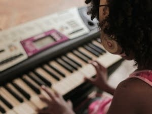 A young girl practicing at the keyboard.