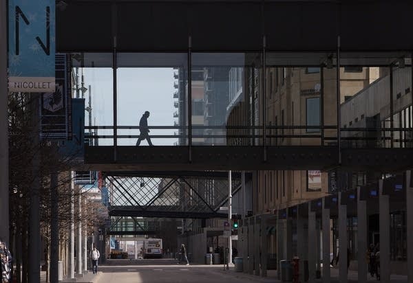 A person walking in a skyway in a quiet downtown.