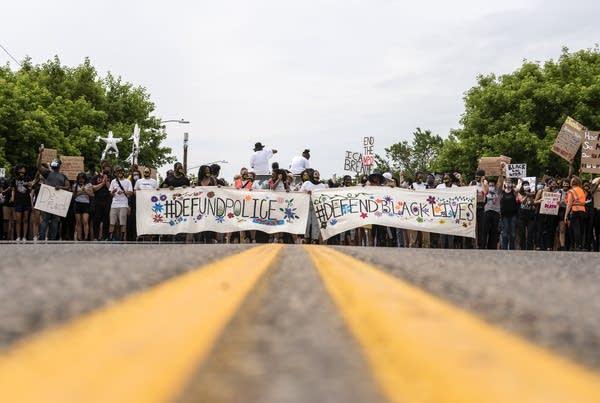 Demonstrators march in the street.