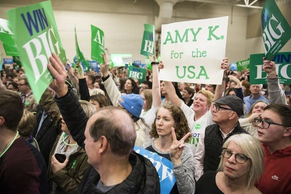 A crowd holds campaign signs for Amy Klobuchar.
