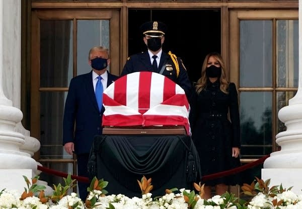 Three people stand behind a flag-draped casket.