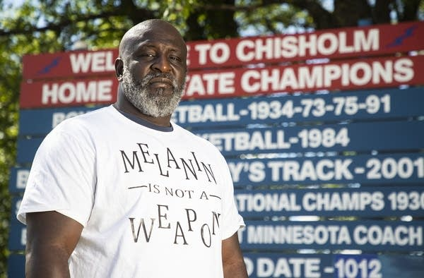 A man standing in front of a high school athletic championship sign.