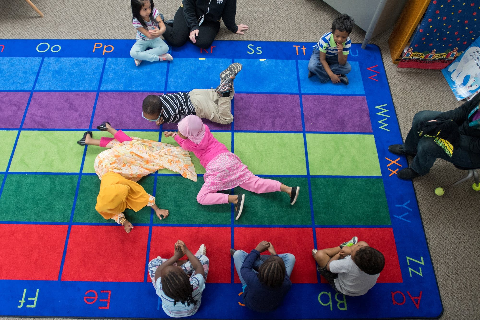 Preschoolers crawl on the carpet as students sing a song about earthworms.