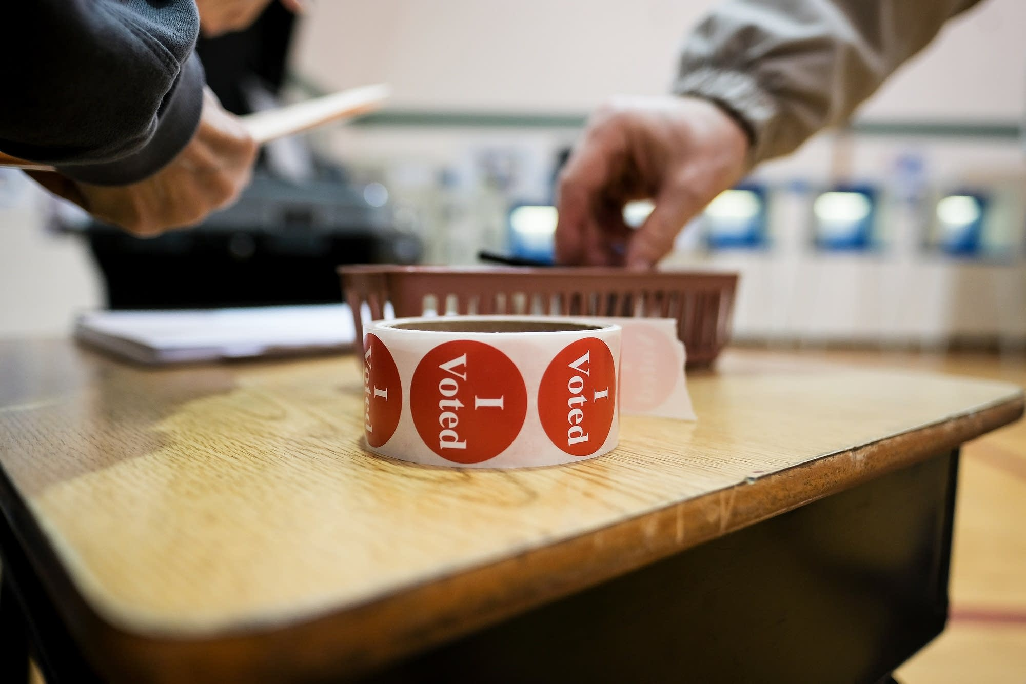 A voter takes a sticker after casting his ballot.