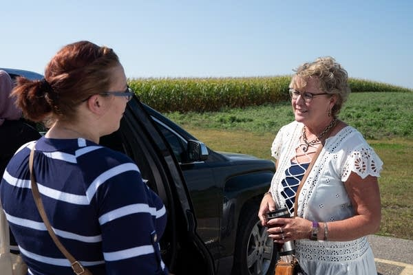 Two women talk to each other next to a car in front of a cornfield.