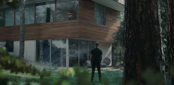 Man standing in yard of beautiful modern home w/ sprinklers on