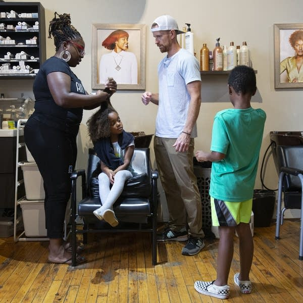 A girls sits in a salon chair as a man, woman and boy stand around her.