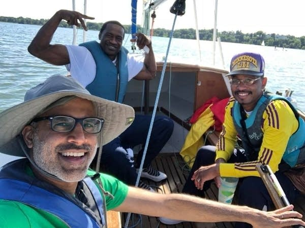 Three men, including George Floyd, on a sailboat.
