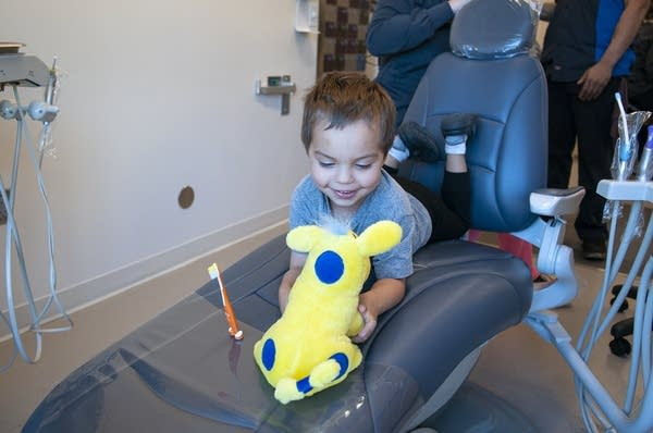 A child plays with a toy while in a dentist's chair.