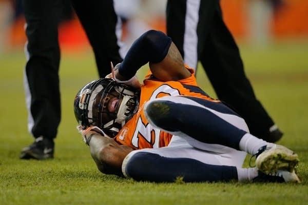 Denver Broncos player David Bruton lies on the gro