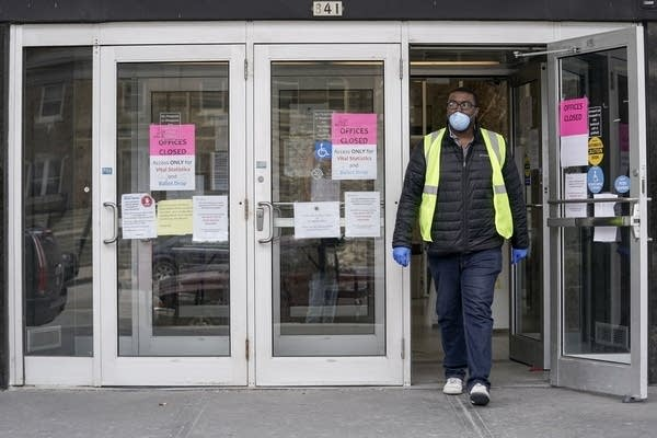 A worker wearing a mask leaves a building in Milwaukee.