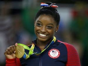 Simone Biles displays her gold medal for floor.