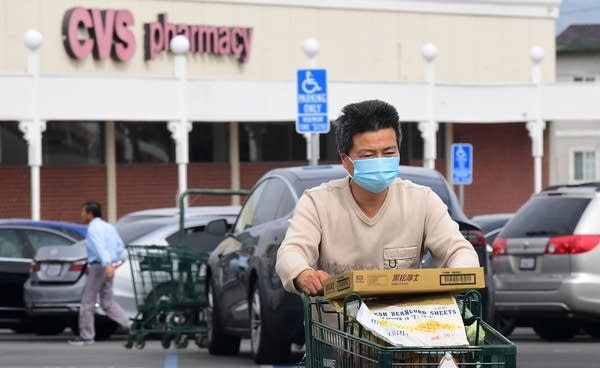 A man wears a facemask while pushing his shopping cart in Alhambra, Calif.