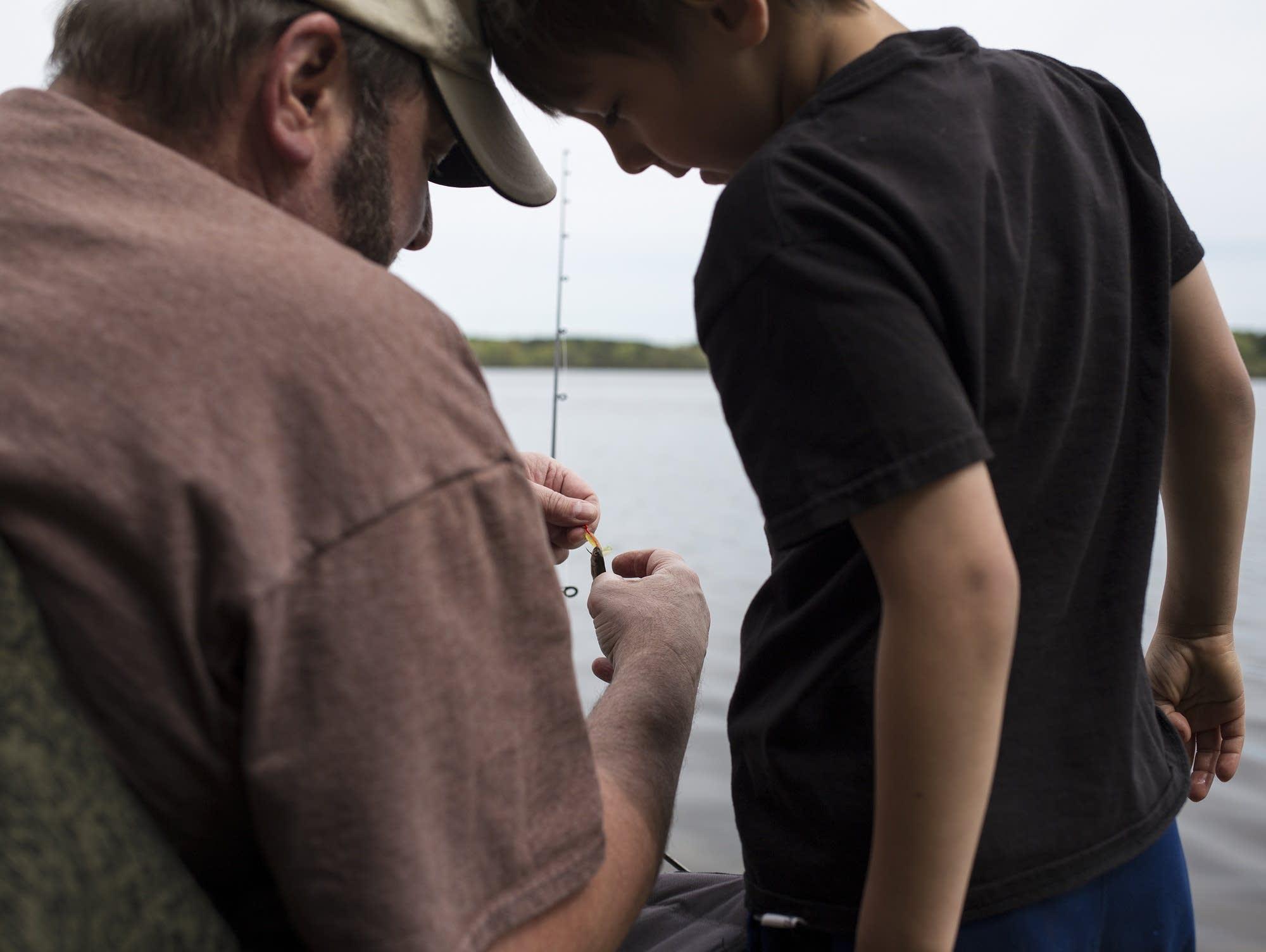 Mike Hoey left of Anoka helps his grandson Hunter Johnson