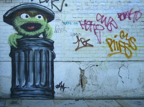 Mural of Oscar the Grouch in garbage can on graffiti covered wall