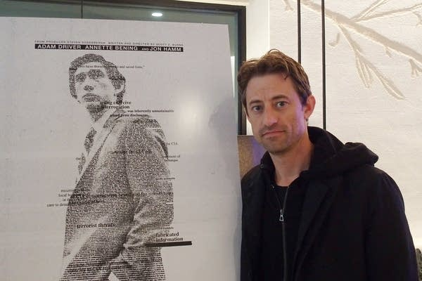 A man stands beside a movie poster.