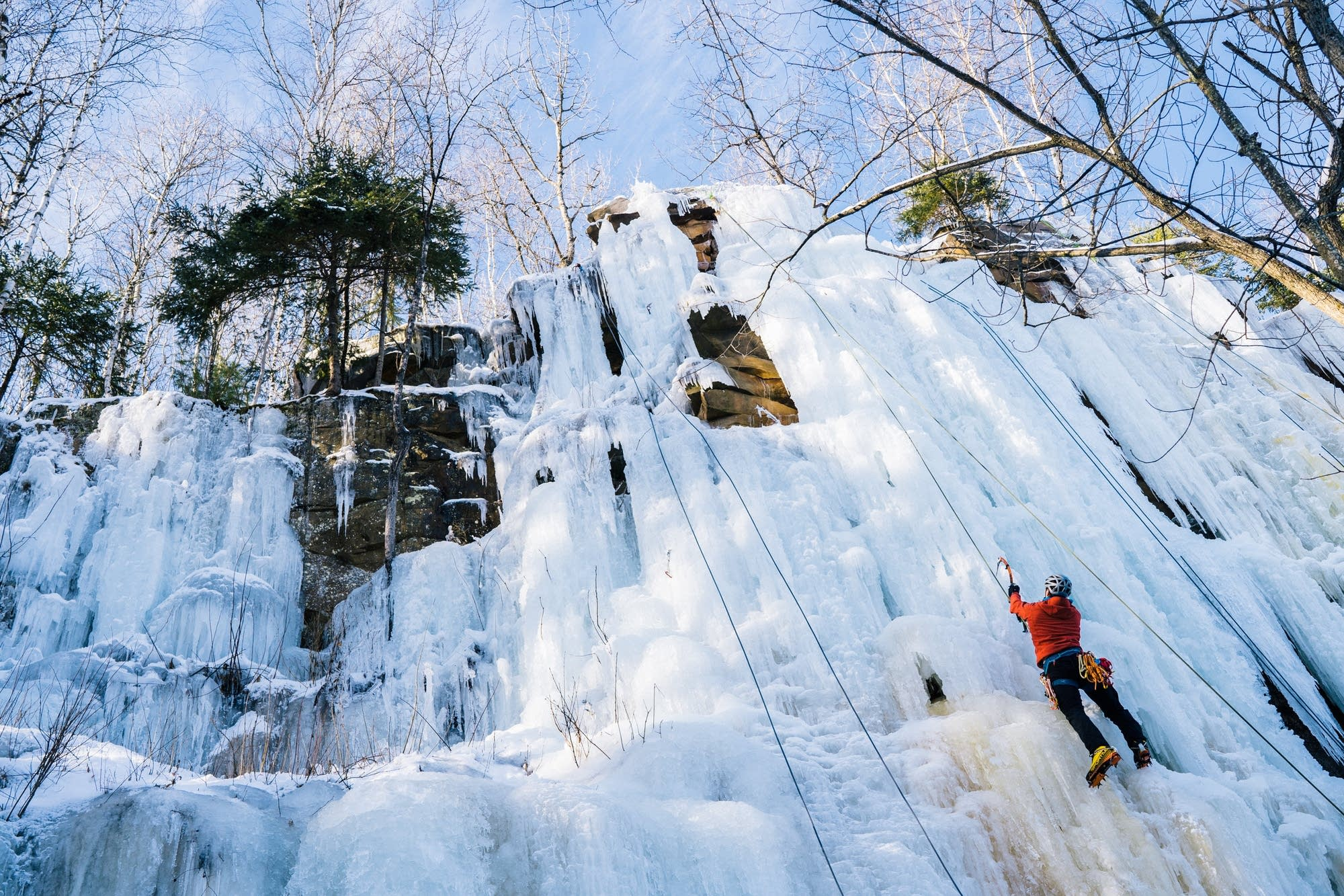 A climber uses crampons and ice picks to scale a wall of ice.
