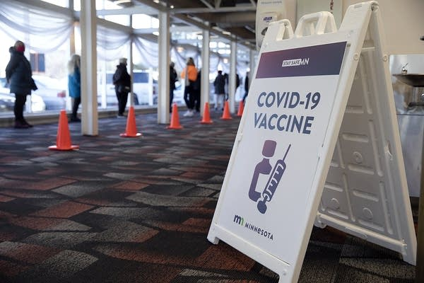 A sign reads covid-19 vaccine near people standing in line.