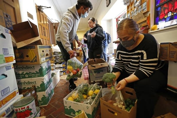 Three people prepare bags of vegetables for food aid.