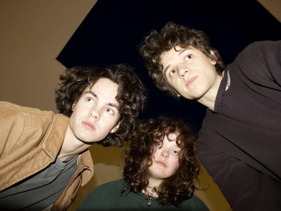 Three people looking down at camera.