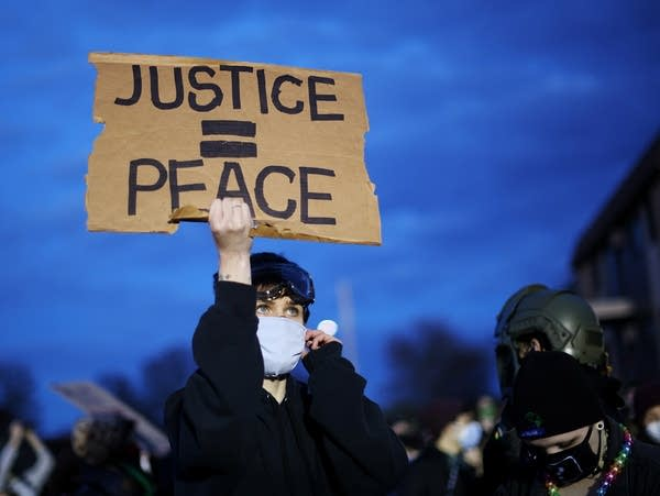 A demonstrator holds up a sign during a protest