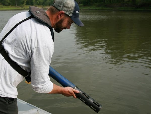 A researcher takes a water sample from a river