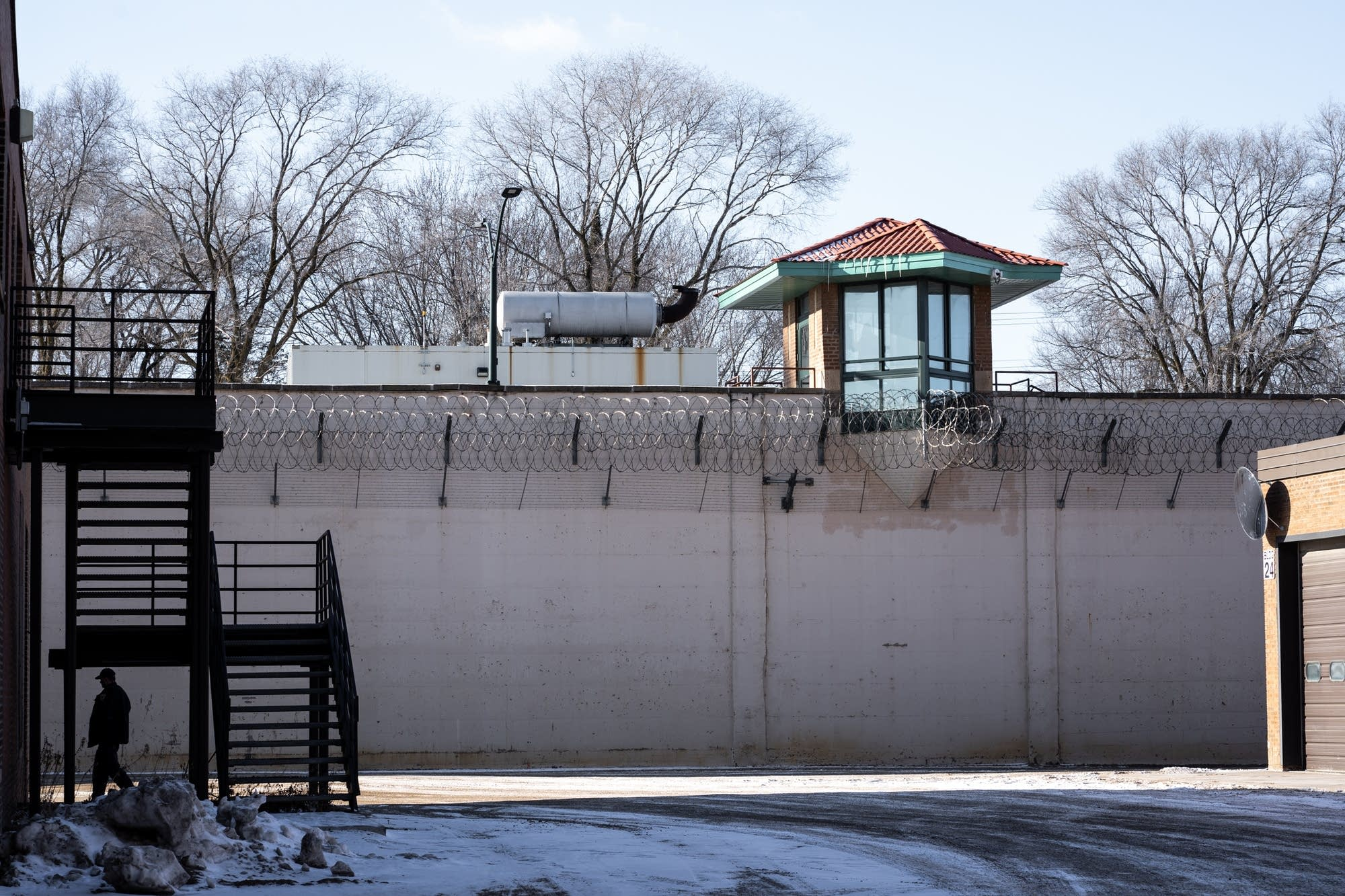 A corrections officer enters a building inside of Stillwater prison.