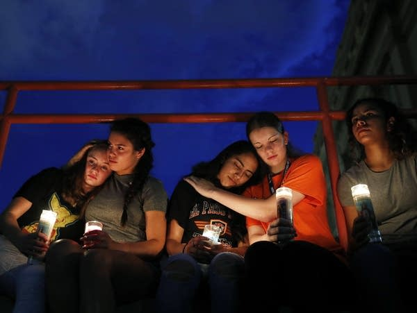 People comfort each other during a vigil for victims of a mass shooting