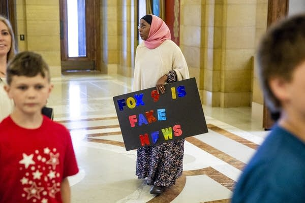Sadia Wasame carries a sign in protest.