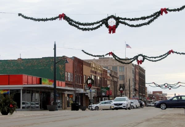 Brick buildings along a street with holiday decorations.