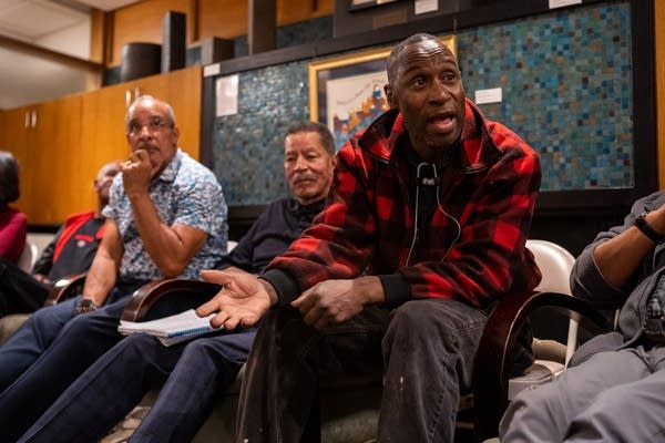 A man in a red flannel sweater leans forward and speaks to the group.