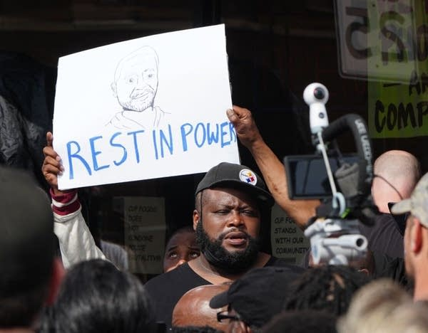"A man holds a side that reads ""rest in power"""