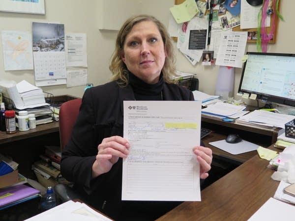 A woman holds a health insurance bill.