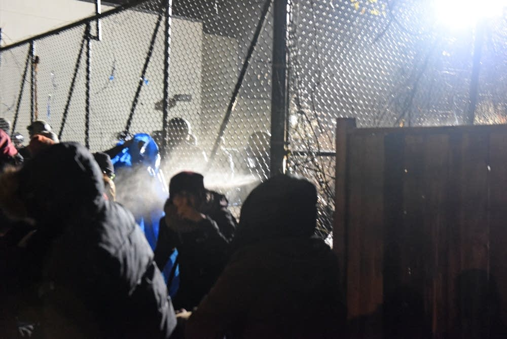 Police shoot a chemical irritant through a fence.