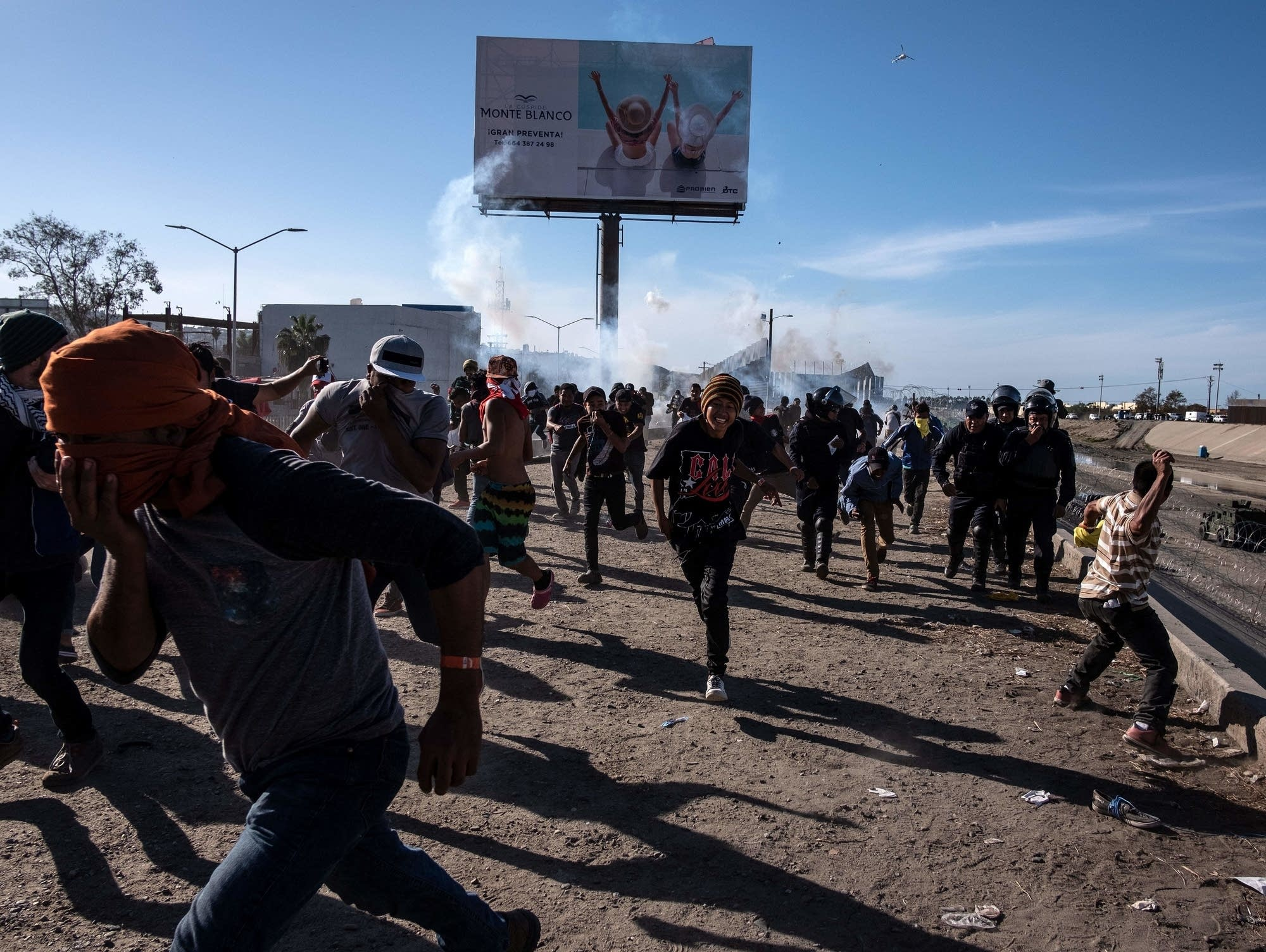 Central American migrants run along the Tijuana River