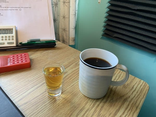 A shot of whiskey next to a cup of coffee on a desk