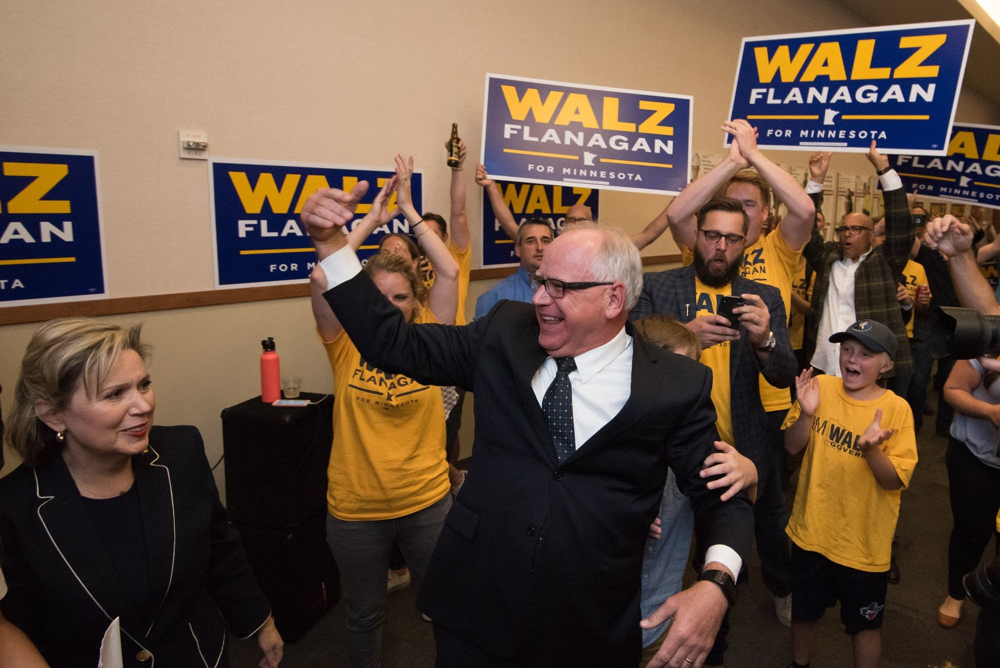 Walz comes out to give a victory speech while supporters cheer.