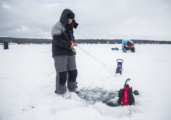 Hannah Hudson ice fishes on the ice over Lake Superior near Washburn, Wis.