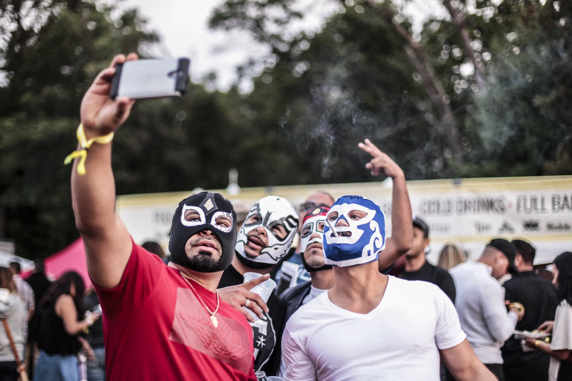 Friends take a selfie in lucha libre masks.