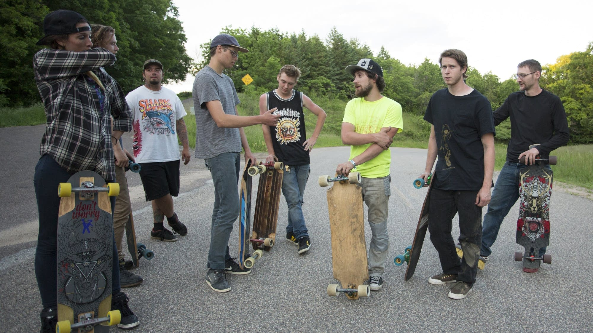 Longboarders gather at the top of a hill.
