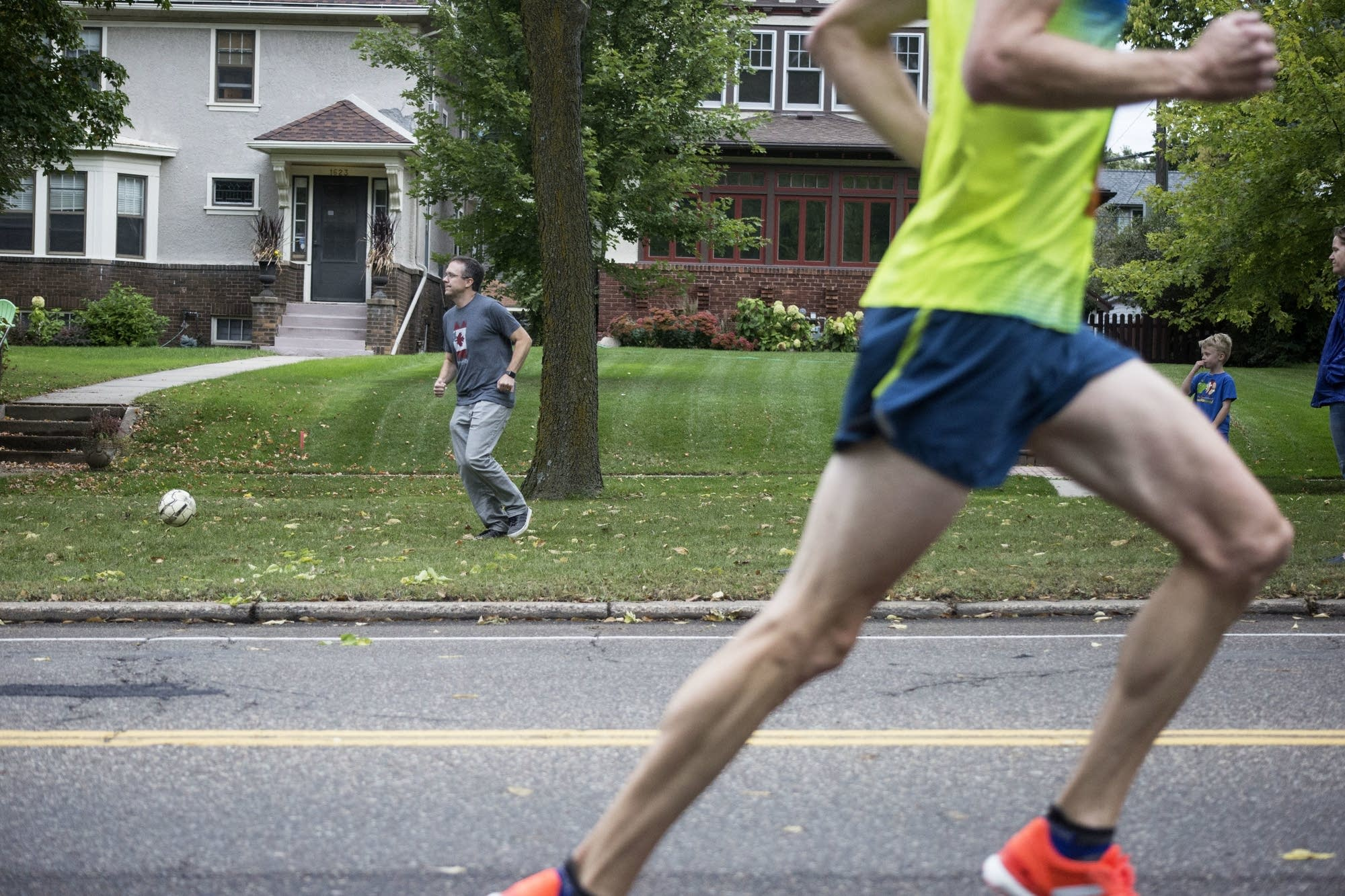 Spectators play as marathon runners pass on Sunday along Summit Avenue.