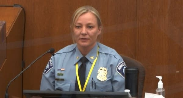 A woman in a police uniform sits in front of a microphone