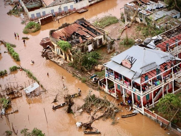 People walk on the flooded streets of Buzi, Mozambique