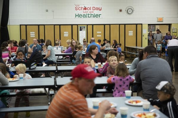 Families sit at tables in a cafeteria