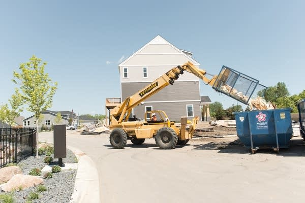 A backhoe dumps a load of scraps on May 25, 2018, at a construction site.