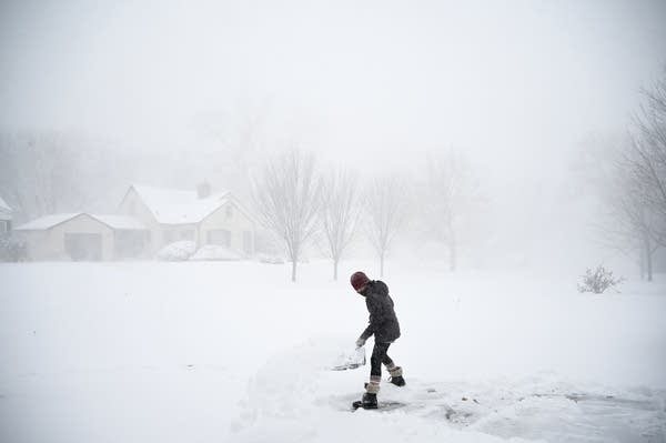 A woman shovels her driveway during a snowstorm.